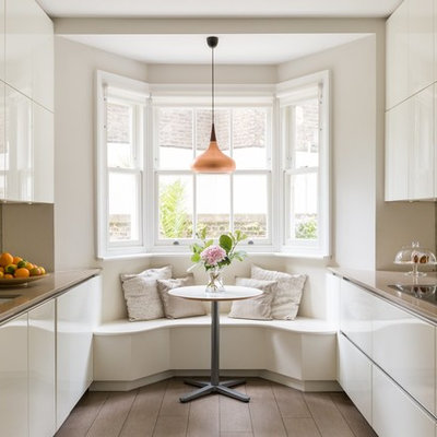 Eat-in kitchen - mid-sized contemporary galley brown floor and dark wood floor eat-in kitchen idea in London with flat-panel cabinets, white cabinets, mirror backsplash, beige countertops, an undermount sink, metallic backsplash, paneled appliances and no island