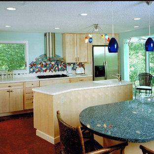 ボストンの広いエクレクティックスタイルのおしゃれなキッチン (一体型シンク、フラットパネル扉のキャビネット、淡色木目調キャビネット、人工大理石カウンター、シルバーの調理設備、コルクフローリング、赤い床) の写真