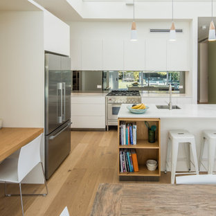 Inspiration for a contemporary l-shaped eat-in kitchen in Sydney with an undermount sink, flat-panel cabinets, white cabinets, stainless steel appliances, with island, brown floor, white benchtop, quartz benchtops, grey splashback, glass sheet splashback and light hardwood floors.