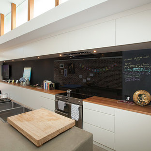 Mid-sized contemporary open concept kitchen ideas - Inspiration for a mid-sized contemporary galley concrete floor open concept kitchen remodel in Sydney with an integrated sink, white cabinets, concrete countertops, black backsplash, glass sheet backsplash, an island and paneled appliances