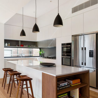 Inspiration for a mid-sized contemporary l-shaped eat-in kitchen in Sydney with flat-panel cabinets, white cabinets, quartz benchtops, grey splashback, ceramic splashback, stainless steel appliances, medium hardwood floors, with island, brown floor and white benchtop.