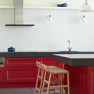 Пример оригинального дизайна: кухня в стиле современная классика с фасадами с утопленной филенкой, красными фасадами, белым фартуком, фартуком из плитки кабанчик, техникой из нержавеющей стали и островом