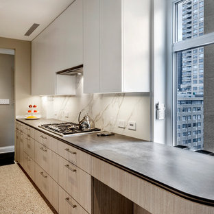 Photo of a large modern galley enclosed kitchen in New York with a submerged sink, flat-panel cabinets, grey cabinets, soapstone worktops, white splashback, stone slab splashback, integrated appliances, lino flooring, no island and multi-coloured floors.