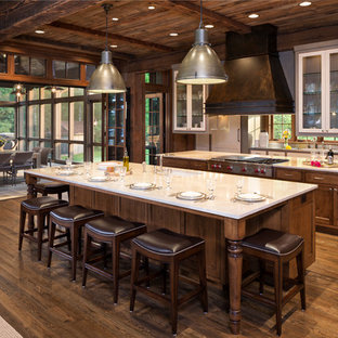 Design ideas for a country kitchen in Denver with shaker cabinets, dark wood cabinets, stainless steel appliances, dark hardwood floors and multiple islands.