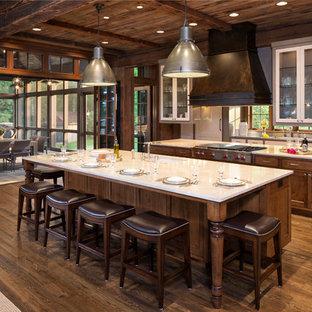 デンバーのラスティックスタイルのおしゃれなマルチアイランドキッチン (シェーカースタイル扉のキャビネット、濃色木目調キャビネット、シルバーの調理設備の、濃色無垢フローリング) の写真