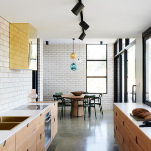 This is an example of a contemporary galley eat-in kitchen in Adelaide with a double-bowl sink, flat-panel cabinets, medium wood cabinets, quartz benchtops, white splashback, brick splashback, stainless steel appliances, concrete floors, no island, grey floor and white benchtop.