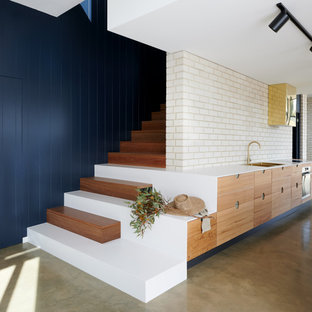 This is an example of a mid-sized contemporary galley kitchen in Adelaide with a double-bowl sink, flat-panel cabinets, medium wood cabinets, quartz benchtops, white splashback, brick splashback, stainless steel appliances, concrete floors, grey floor and white benchtop.