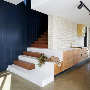 アデレードの中くらいのコンテンポラリースタイルのおしゃれなII型キッチン (ダブルシンク、フラットパネル扉のキャビネット、中間色木目調キャビネット、クオーツストーンカウンター、白いキッチンパネル、レンガのキッチンパネル、シルバーの調理設備、コンクリートの床、グレーの床、白いキッチンカウンター) の写真