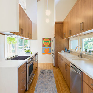 Mid-sized midcentury galley separate kitchen in Minneapolis with an integrated sink, flat-panel cabinets, brown cabinets, solid surface benchtops, stainless steel appliances, light hardwood floors, with island, brown floor and white benchtop.