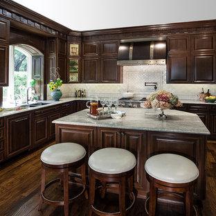 Пример оригинального дизайна: большая п-образная кухня-гостиная в классическом стиле с врезной раковиной, фасадами с утопленной филенкой, темными деревянными фасадами, гранитной столешницей, белым фартуком, фартуком из терракотовой плитки, техникой под мебельный фасад, паркетным полом среднего тона и островом