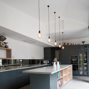 Inredning av ett modernt mellanstort grå grått kök, med bänkskiva i betong, spegel som stänkskydd, svarta vitvaror, en köksö, betonggolv och grått golv