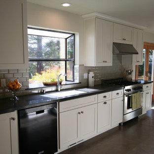 サンフランシスコの中くらいのトラディショナルスタイルのおしゃれなキッチン (アンダーカウンターシンク、落し込みパネル扉のキャビネット、ベージュのキャビネット、ラミネートカウンター、グレーのキッチンパネル、セラミックタイルのキッチンパネル、シルバーの調理設備、トラバーチンの床) の写真