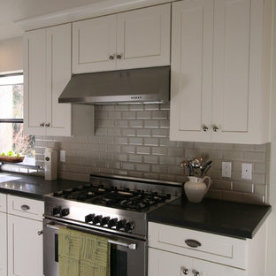 Inspiration for a mid-sized traditional u-shaped eat-in kitchen in San Francisco with an undermount sink, recessed-panel cabinets, beige cabinets, laminate benchtops, grey splashback, ceramic splashback, stainless steel appliances and travertine floors.