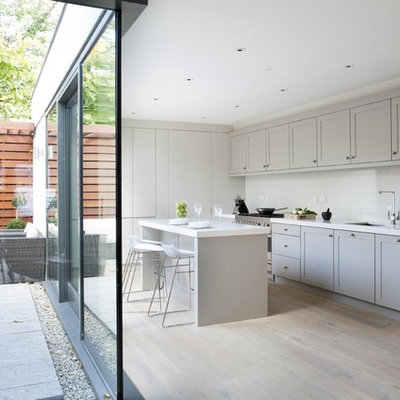 Inspiration for a contemporary l-shaped kitchen remodel in Dublin with an undermount sink, shaker cabinets, gray cabinets, white backsplash, glass sheet backsplash and stainless steel appliances