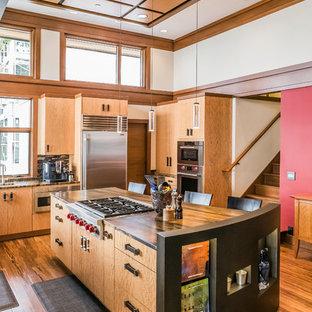 Foto de cocina vintage, de tamaño medio, con armarios con paneles lisos, puertas de armario de madera oscura, electrodomésticos de acero inoxidable, suelo de madera en tonos medios y una isla