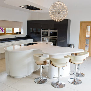 Ejemplo de cocina comedor en L, contemporánea, grande, con fregadero bajoencimera, puertas de armario blancas, encimera de acrílico, suelo de travertino, una isla y armarios con paneles lisos