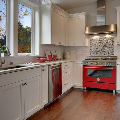 Example of a transitional open concept kitchen design in Seattle with recessed-panel cabinets, white cabinets, black backsplash, colored appliances and an undermount sink