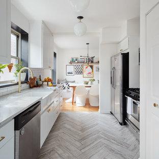 Geschlossene, Zweizeilige, Mittelgroße Klassische Küche ohne Insel mit Landhausspüle, flächenbündigen Schrankfronten, weißen Schränken, Marmor-Arbeitsplatte, Küchenrückwand in Weiß, Rückwand aus Porzellanfliesen, Küchengeräten aus Edelstahl, Travertin und grauem Boden in Chicago