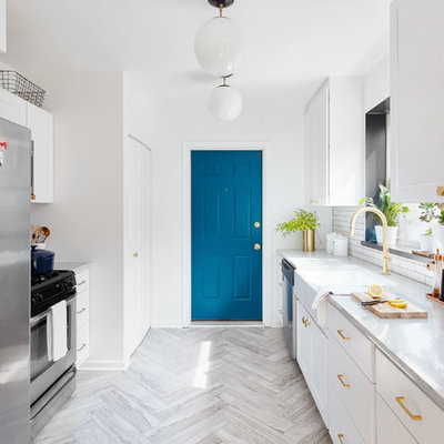 Inspiration for a mid-sized transitional galley travertine floor and gray floor enclosed kitchen remodel in Chicago with a farmhouse sink, white cabinets, white backsplash, stainless steel appliances, no island, flat-panel cabinets, marble countertops and porcelain backsplash