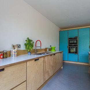 サセックスの大きいエクレクティックスタイルのおしゃれなキッチン (ダブルシンク、オープンシェルフ、淡色木目調キャビネット、ラミネートカウンター、ベージュキッチンパネル、木材のキッチンパネル、黒い調理設備、コンクリートの床、グレーの床、白いキッチンカウンター) の写真