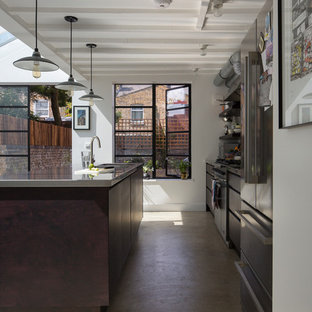 Contemporary kitchen in London with stainless steel worktops, stainless steel appliances, an island and concrete flooring.