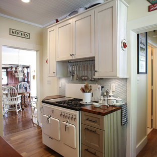 Mid-sized victorian enclosed kitchen remodeling - Example of a mid-sized ornate u-shaped medium tone wood floor enclosed kitchen design in Other with shaker cabinets, wood countertops, a farmhouse sink, white cabinets, blue backsplash, glass tile backsplash, white appliances and an island