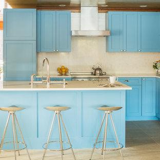 Идея дизайна: угловая кухня в стиле современная классика с фасадами в стиле шейкер, синими фасадами, столешницей из кварцевого агломерата, техникой из нержавеющей стали, островом, врезной раковиной и бежевым фартуком