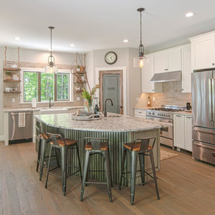 Example of a mid-sized arts and crafts l-shaped medium tone wood floor and brown floor open concept kitchen design in Portland Maine with a farmhouse sink, beaded inset cabinets, white cabinets, granite countertops, beige backsplash, stone tile backsplash, stainless steel appliances and an island