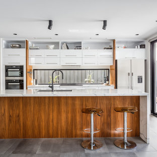 This is an example of a contemporary galley open plan kitchen in Perth with flat-panel cabinets, white cabinets, marble benchtops, window splashback, black appliances, with island and grey floor.