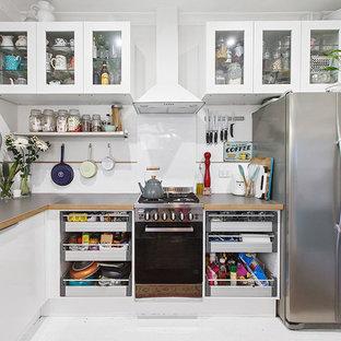 メルボルンの小さいエクレクティックスタイルのおしゃれなキッチン (エプロンフロントシンク、オープンシェルフ、白いキャビネット、ラミネートカウンター、白いキッチンパネル、セラミックタイルのキッチンパネル、シルバーの調理設備の、淡色無垢フローリング、白い床、グレーのキッチンカウンター) の写真