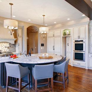 Idee per una cucina classica di medie dimensioni con lavello sottopiano, ante con riquadro incassato, ante beige, paraspruzzi multicolore, paraspruzzi con piastrelle a mosaico, elettrodomestici in acciaio inossidabile, pavimento in legno massello medio, isola e top in granito