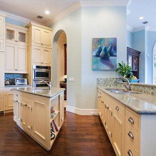 Réalisation d'une grande cuisine ouverte bohème avec des portes de placard blanches, un plan de travail en granite, une crédence bleue, une crédence en mosaïque, un électroménager en acier inoxydable, un sol en bois brun, un îlot central et un évier 3 bacs.