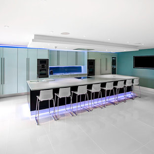 Photo of a large modern single-wall kitchen/diner in London with an integrated sink, flat-panel cabinets, blue cabinets, composite countertops, blue splashback, glass sheet splashback, coloured appliances, porcelain flooring and an island.