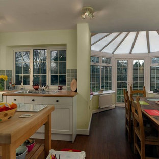 This is an example of a mid-sized traditional l-shaped eat-in kitchen in Buckinghamshire with a drop-in sink, recessed-panel cabinets, white cabinets, wood benchtops, green splashback, ceramic splashback, laminate floors, with island, brown floor and orange benchtop.