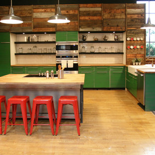 Industrial open concept kitchen ideas - Urban u-shaped open concept kitchen photo in Portland with a farmhouse sink, flat-panel cabinets, green cabinets, wood countertops, beige backsplash, subway tile backsplash and stainless steel appliances