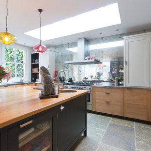 Удачное сочетание для дизайна помещения: большая п-образная кухня-гостиная в современном стиле с монолитной раковиной, фасадами в стиле шейкер, черными фасадами, столешницей из нержавеющей стали, фартуком цвета металлик, фартуком из стеклянной плитки, техникой из нержавеющей стали, полом из терраццо и островом - самое интересное для вас