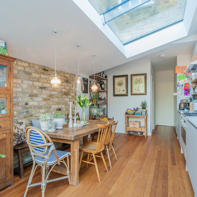 Eat-in kitchen - mid-sized transitional single-wall medium tone wood floor eat-in kitchen idea in London with an undermount sink, flat-panel cabinets, beige cabinets, quartzite countertops, colored appliances and no island