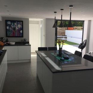 ロンドンの中くらいのヴィクトリアン調のおしゃれなキッチン (ドロップインシンク、フラットパネル扉のキャビネット、白いキャビネット、珪岩カウンター、緑のキッチンパネル、ガラス板のキッチンパネル、シルバーの調理設備、磁器タイルの床、グレーの床) の写真