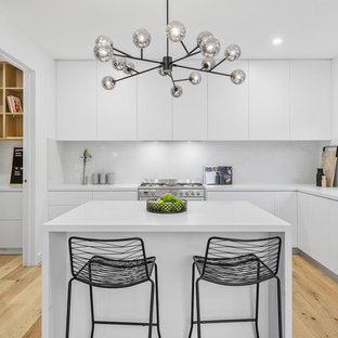 Photo of a small contemporary l-shaped eat-in kitchen in Melbourne with white cabinets, quartz benchtops, white splashback, marble splashback, stainless steel appliances, light hardwood floors, with island, white benchtop, a double-bowl sink, flat-panel cabinets and beige floor.