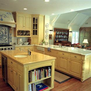 Diseño de cocina rural con puertas de armario amarillas, armarios con rebordes decorativos y salpicadero azul