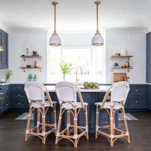 Traditional eat-in kitchen designs - Example of a classic u-shaped dark wood floor and brown floor eat-in kitchen design in Houston with a farmhouse sink, blue cabinets, white backsplash, stainless steel appliances, an island, white countertops and shaker cabinets