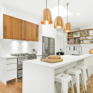 This is an example of a mid-sized contemporary galley open plan kitchen in Melbourne with an undermount sink, flat-panel cabinets, white cabinets, quartz benchtops, white splashback, stainless steel appliances, medium hardwood floors, with island, white benchtop and beige floor.