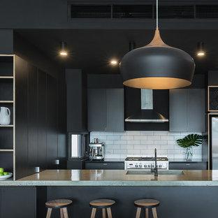 Modelo de cocina en U, urbana, pequeña, abierta, con fregadero integrado, puertas de armario negras, encimera de cemento, salpicadero blanco, salpicadero de azulejos tipo metro, electrodomésticos de acero inoxidable, suelo de cemento y península