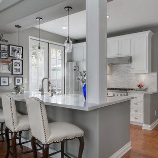 Zweizeilige, Kleine Moderne Wohnküche mit Landhausspüle, Schrankfronten im Shaker-Stil, weißen Schränken, Quarzwerkstein-Arbeitsplatte, Küchenrückwand in Grau, Rückwand aus Mosaikfliesen, Küchengeräten aus Edelstahl und Kücheninsel in Orange County