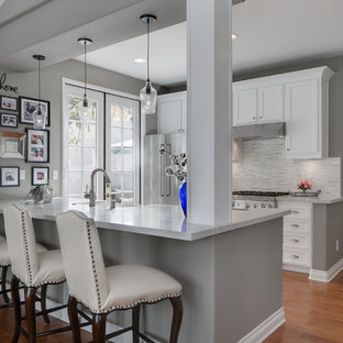 Small contemporary eat-in kitchen appliance - Inspiration for a small contemporary galley eat-in kitchen remodel in Orange County with a farmhouse sink, shaker cabinets, white cabinets, quartz countertops, gray backsplash, mosaic tile backsplash, stainless steel appliances and an island