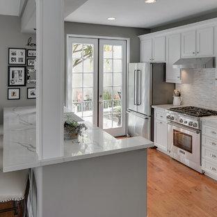 Inredning av ett modernt litet kök, med en rustik diskho, skåp i shakerstil, vita skåp, bänkskiva i kvarts, grått stänkskydd, stänkskydd i mosaik, rostfria vitvaror och en köksö