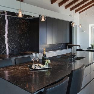 Esempio di una grande cucina contemporanea con lavello sottopiano, ante lisce, ante grigie, top in onice, paraspruzzi nero, paraspruzzi in lastra di pietra, elettrodomestici da incasso, pavimento in cemento, isola, pavimento nero e top nero