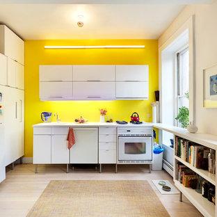 Inspiration för avskilda, små moderna l-kök, med vita skåp, gult stänkskydd, vita vitvaror, ljust trägolv och släta luckor
