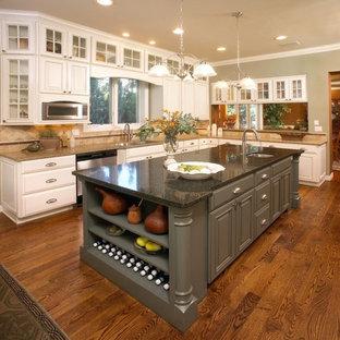 Große Klassische Küche in L-Form mit profilierten Schrankfronten, weißen Schränken, Küchengeräten aus Edelstahl, braunem Holzboden, Kücheninsel, Unterbauwaschbecken, Granit-Arbeitsplatte, Küchenrückwand in Beige, Rückwand aus Keramikfliesen und braunem Boden in Denver