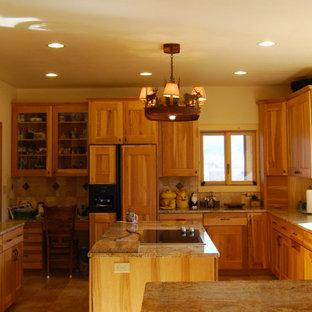 デンバーの大きいラスティックスタイルのおしゃれなキッチン (アンダーカウンターシンク、シェーカースタイル扉のキャビネット、中間色木目調キャビネット、御影石カウンター、ベージュキッチンパネル、トラバーチンの床、パネルと同色の調理設備、トラバーチンの床、ベージュの床) の写真
